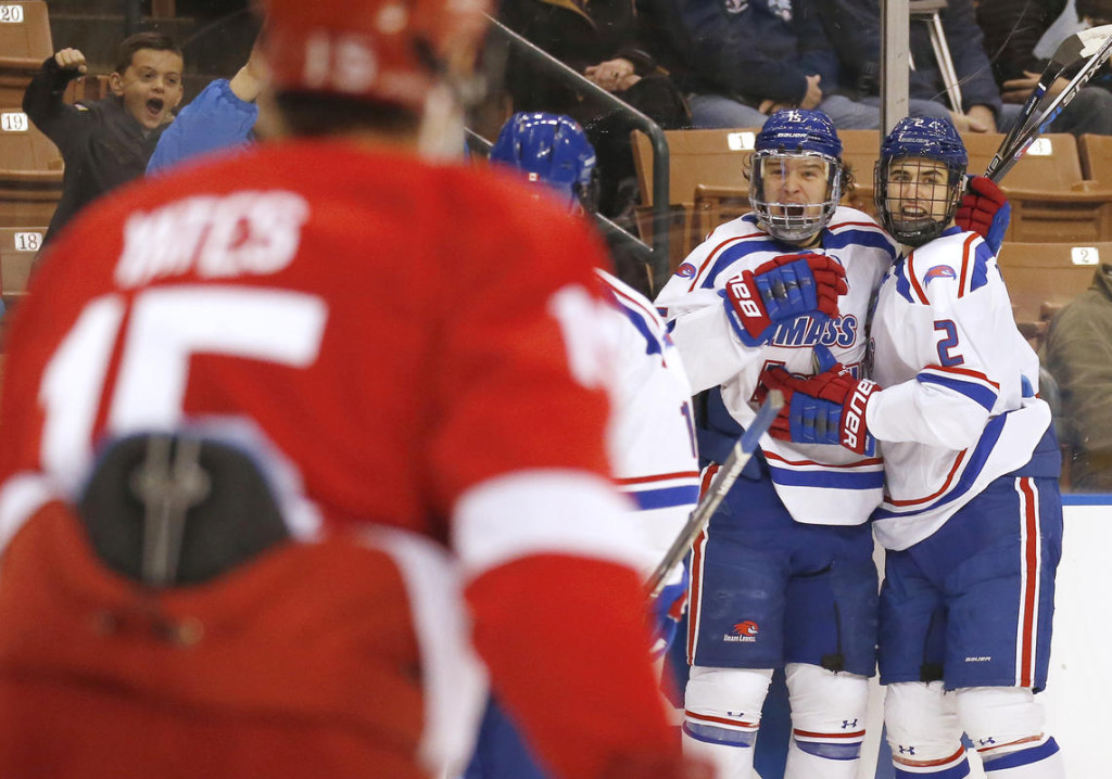 UMass Lowell freshman forward Ryan Dmowski (in the center in white) of East Lynne, CT, is congratulated by teammates including Tommy Panico (2) after scoring the first goal of the game, en route to a 5-0 smothering of  Cornell, during the first period of an NCAA regional men's college hockey tournament game, Saturday, in Manchester, N.H.  Lowell advances to play the winner of today's late game between Minnesota and Notre Dame, tomorrow at 12:30PM Pacific Time on ESPNU.